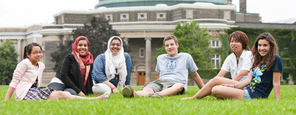 A smiling, diverse group of U of T students sit on the grassy field in front of Convocation Hall in summer