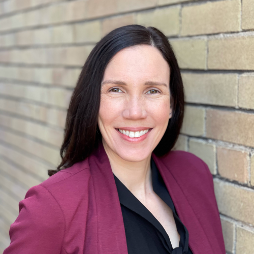 Photo of Professor Jennifer Campbell standing against a brick wall in a maroon blazer and black shirt.